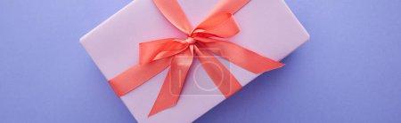 Foto de Vista superior de la caja de regalo violeta con cinta roja y arco en fondo púrpura, tiro panorámico. - Imagen libre de derechos