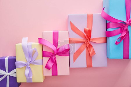 Photo for Flat lay with colorful gift boxes with ribbons and bows scattered on pink background with copy space - Royalty Free Image