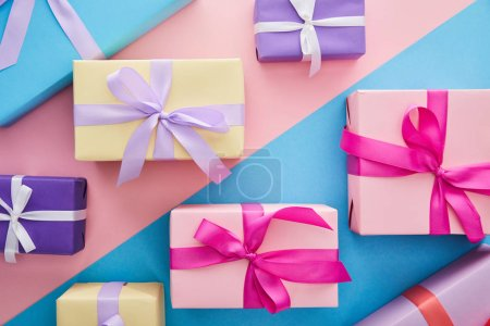 Photo for Top view of colorful gift boxes with ribbons and bows on blue and pink background - Royalty Free Image
