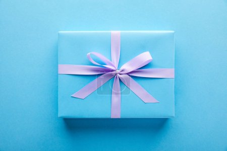 top view of blue gift with violet ribbon on blue background