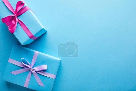 Photo pour Vue du dessus des boîtes-cadeaux colorées sur fond bleu avec espace de copie - image libre de droit