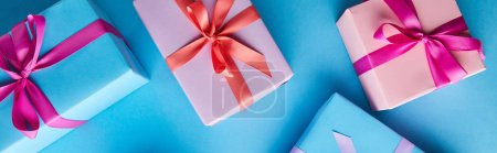 Photo pour Top view of colorful gift boxes on blue background, panoramic shot - image libre de droit