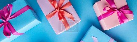 Photo pour Vue de dessus des boîtes-cadeaux colorées sur fond bleu, panoramique - image libre de droit