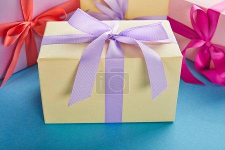 Photo pour Boîtes-cadeaux colorées avec rubans et archets sur fond bleu - image libre de droit