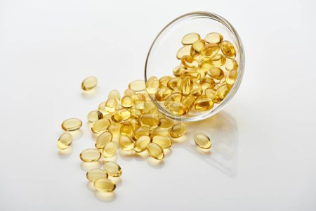 Photo for Golden fish oil capsules in glass bowl on white background - Royalty Free Image