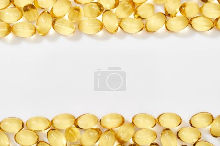 Photo for Top view of golden fish oil capsules arranged in frame on white background - Royalty Free Image