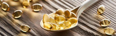 Photo for Golden fish oil capsules in spoon on wooden table, panoramic shot - Royalty Free Image