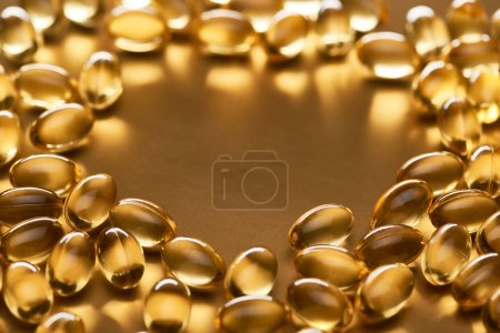 Photo for Close up view of shiny fish oil capsules on golden background with copy space - Royalty Free Image