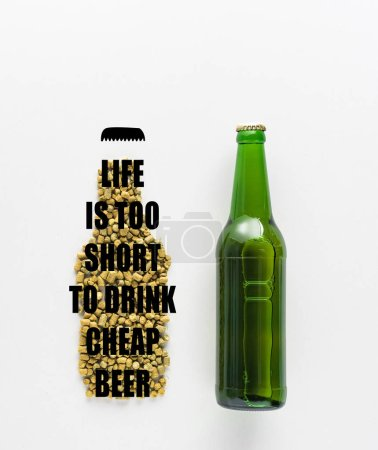 top view of bottle of beer near pressed hop with life is too short to drink cheap beer lettering isolated on white