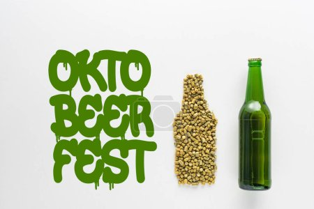 top view of bottle of beer near pressed hop and green Oktoberfest lettering isolated on white