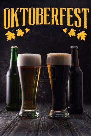 Photo pour Verres de bière fraîche claire et foncée près des bouteilles sur table en bois avec lettrage Oktoberfest jaune - image libre de droit