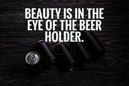 Photo pour Boîtes de bière en aluminium noir sur table en bois avec de la beauté est dans l'oeil de l'illustration porte-bière - image libre de droit