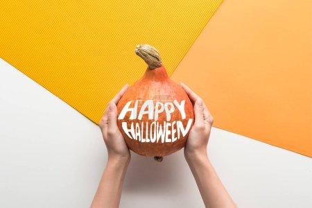 Photo pour Vue recadrée de la femme tenant citrouille mûre avec heureuse illustration Halloween sur fond blanc et orange - image libre de droit
