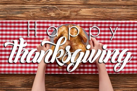 cropped view of woman holding roasted turkey on red plaid napkin on wooden table with happy thanksgiving illustration