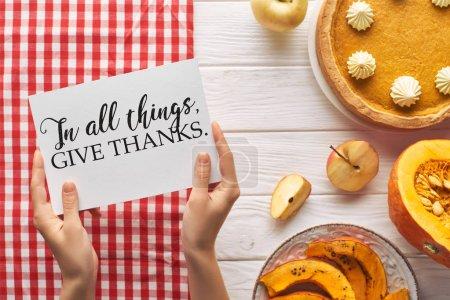 vista parcial de la mujer que sostiene la tarjeta con en todas las cosas dar gracias ilustración cerca de pastel de calabaza en la mesa blanca de madera con manzanas y servilleta roja a cuadros