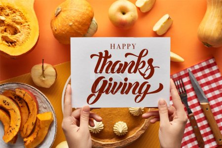 Photo for Cropped view of woman holding card near with happy thanksgiving illustration pumpkin pie on orange background - Royalty Free Image