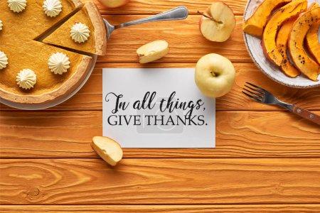 Photo pour Vue de dessus de délicieuse tarte à la citrouille, pommes et carte avec en toutes choses donner illustration de remerciements sur table orange en bois - image libre de droit