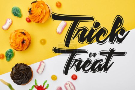 Photo for Top view of colorful gummy sweets and cupcakes on yellow and white background with trick or treat illustration - Royalty Free Image