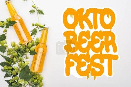 Photo pour Vue du dessus de la bière en bouteilles avec houblon vert sur fond blanc avec lettrage Oktoberfest orange - image libre de droit