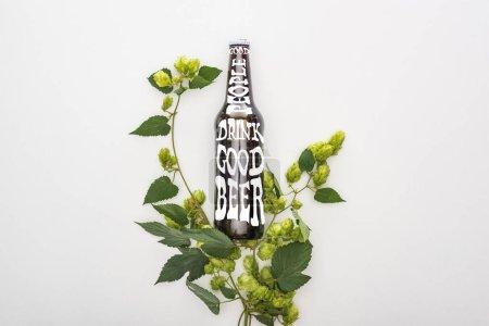 Photo pour Vue du dessus de la bière en bouteille avec de bonnes personnes boire une bonne bière lettrage et vert floraison hop sur fond blanc - image libre de droit
