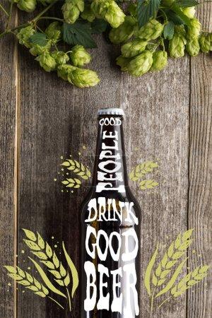 верхний вид свежего пива в бутылке с хорошими людьми пить хорошее пиво буквы около зеленого хмеля на деревянной поверхности