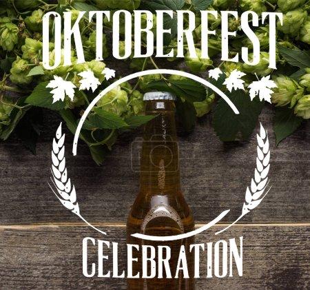 Photo pour Vue du dessus de la bière fraîche en bouteille avec houblon vert sur la surface en bois avec illustration de célébration Oktoberfest - image libre de droit