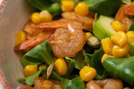 Nahaufnahme von frischem grünen Salat mit Kürbiskernen, Mais, Garnelen und Avocado