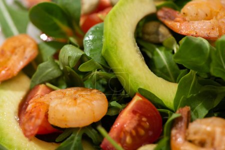 close up view of fresh green salad with cherry tomatoes, shrimps and avocado