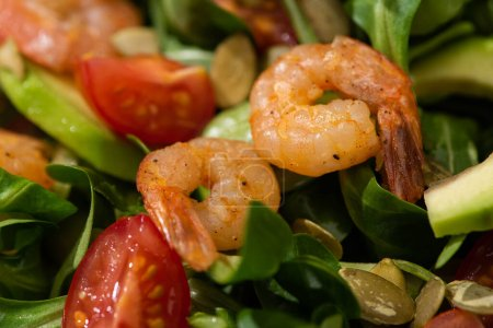 Photo pour Vue rapprochée de la salade verte fraîche aux graines de citrouille, tomates cerises, crevettes et avocat - image libre de droit