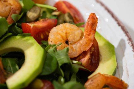 Photo pour Vue rapprochée de la salade verte fraîche avec des graines de citrouille, tomates cerises, crevettes et avocat dans l'assiette - image libre de droit