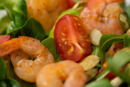 Photo for Close up view of fresh green salad with pumpkin seeds, cherry tomatoes, shrimps and avocado - Royalty Free Image