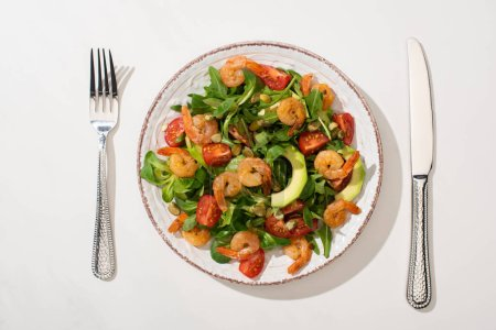 Photo for Top view of fresh green salad with shrimps and avocado on plate near cutlery on white background - Royalty Free Image