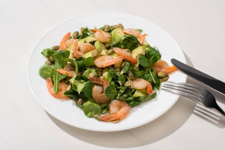 fresh green salad with pumpkin seeds, shrimps and avocado on plate near cutlery on white background