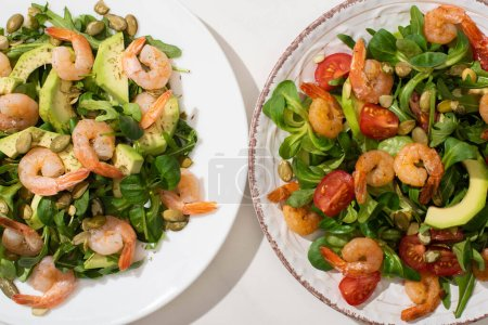 Photo for Top view of fresh green salad with shrimps and avocado on plates - Royalty Free Image