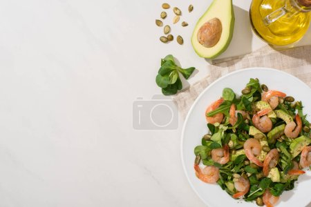 Photo for Top view of fresh green salad with pumpkin seeds, shrimps and avocado on plate on napkin near ingredients on white background - Royalty Free Image