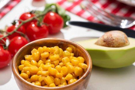 selective focus of fresh avocado, corn and cherry tomatoes