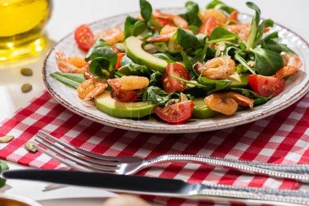 selektiver Schwerpunkt frischer grüner Salat mit Garnelen und Avocado auf Teller neben Besteck auf karierter Serviette