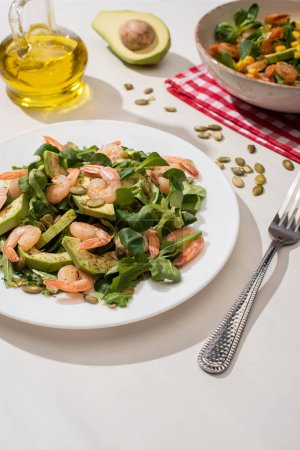 Photo for Selective focus of fresh green salad with shrimps and avocado on plates near fork and oil - Royalty Free Image