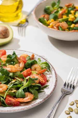 Photo for Selective focus of fresh green salad with shrimps and avocado on plates near forks on white background - Royalty Free Image