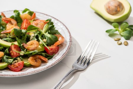 Photo for Selective focus of fresh green salad with shrimps and avocado on plate near fork and ingredients on white background - Royalty Free Image