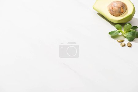 Photo for Fresh green avocado, green leaves and pumpkin seeds on white background - Royalty Free Image
