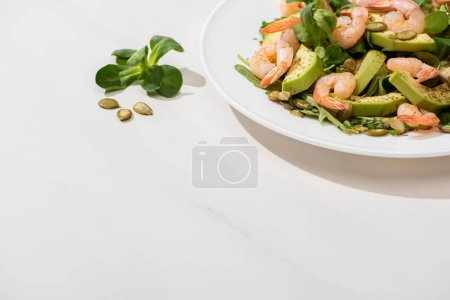 fresh green salad with shrimps and avocado on plate on white background