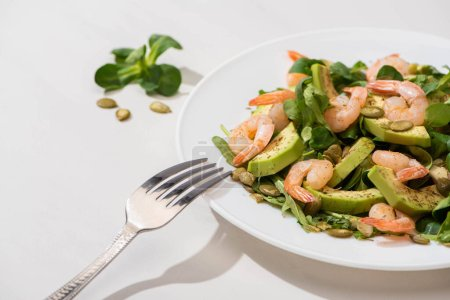 Photo for Selective focus of fresh green salad with shrimps and avocado on plate near fork on white background - Royalty Free Image