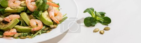 fresh green salad with shrimps and avocado on plate on white background, horizontal image