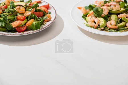 Photo for Fresh green salad with shrimps and avocado on plates  on white background - Royalty Free Image