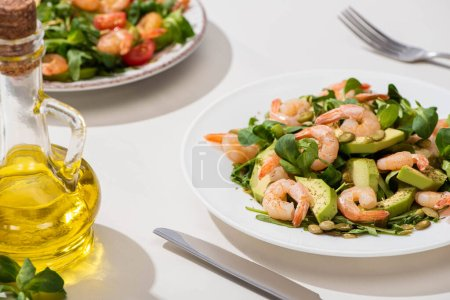 Photo for Selective focus of fresh green salad with shrimps and avocado on plate near olive oil and cutlery on white background - Royalty Free Image