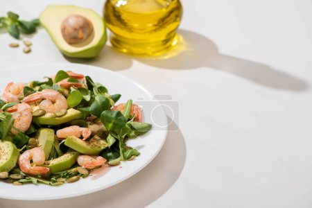 Photo for Selective focus of fresh green salad with shrimps and avocado on plate near olive oil on white background - Royalty Free Image