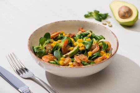 selektiver Schwerpunkt von frischem grünem Salat mit Mais, Garnelen und Avocado auf Teller neben Besteck auf weißem Hintergrund