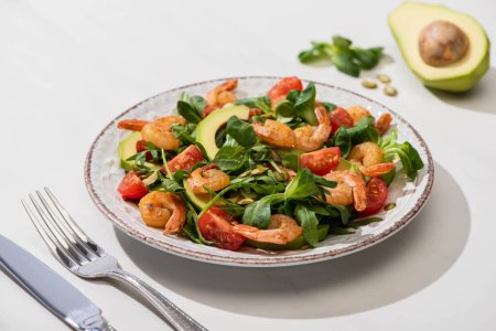 Photo for Selective focus of fresh green salad with shrimps and avocado on plate near cutlery on white background - Royalty Free Image