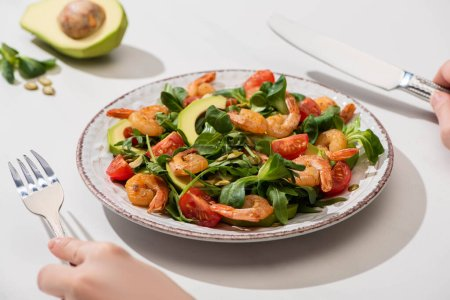 Photo for Partial view of woman eating fresh green salad with cherry tomatoes, shrimps and avocado on white background - Royalty Free Image